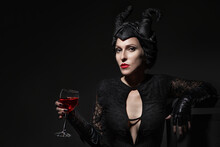 Beautiful And Fashionable Brunette Slim Model Girl In The Image Of Maleficent With Wine Glass In Her Hands  Against Dark Background