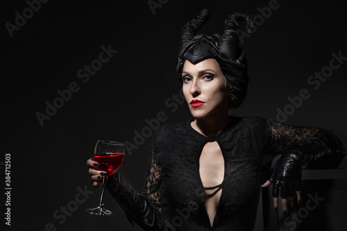 Fototapeta Beautiful and fashionable brunette slim model girl in the image of Maleficent wi