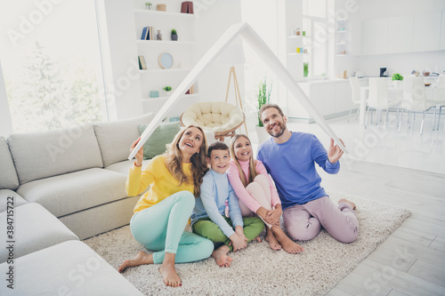 Full body photo of harmony family people mommy daddy sit floor hold paper card roof above two little kids in house indoors