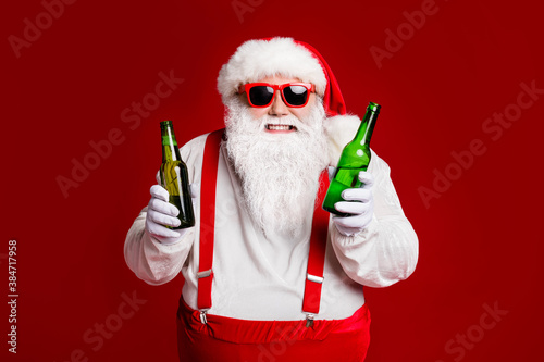 Obraz Portrait of his he attractive cheerful cheery funny fat white-haired Santa holding in hand beer bottles invite festal event isolated bright vivid shine vibrant red burgundy maroon color background - fototapety do salonu