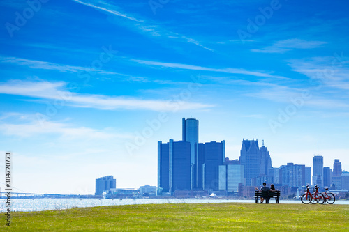 Fotografía Detroit river with view of downtown and lovely couple sit in the bench on Sunset
