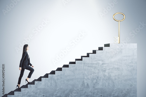 Obraz Businessman in suit climbing stairs with golden key - fototapety do salonu