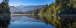 Fox glacier. Mountains. Lake Matheson mirror lake; New Zealand. Oceania. Morninglight. Panorama. Snow covered mountains. Forest. Reflections.