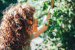 Portrait of young woman with curly hair enjoying scent of blooming tree flowers