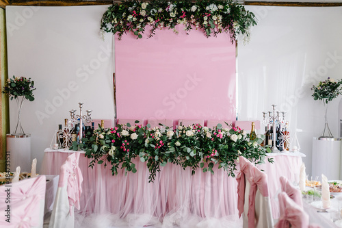 Fotografie, Obraz Festive table, arch, stands decorated with composition of pink flowers and greenery, candles in the banquet hall