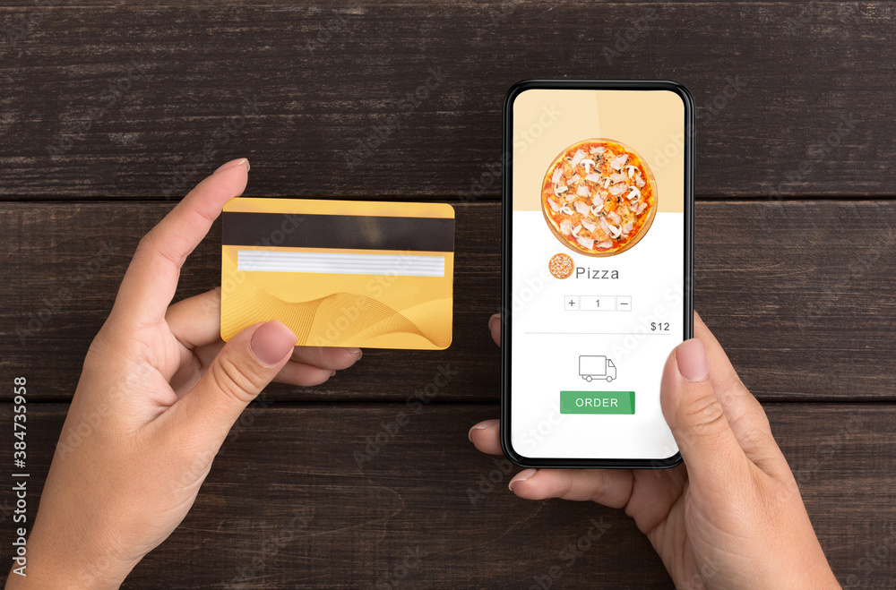 Fototapeta Application for ordering food and contactless payment during quarantine. Female hands hold smartphone