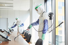 Side View Portrait Of Two Workers Wearing Hazmat Suits Disinfecting Conference Room In Office, Copy Space