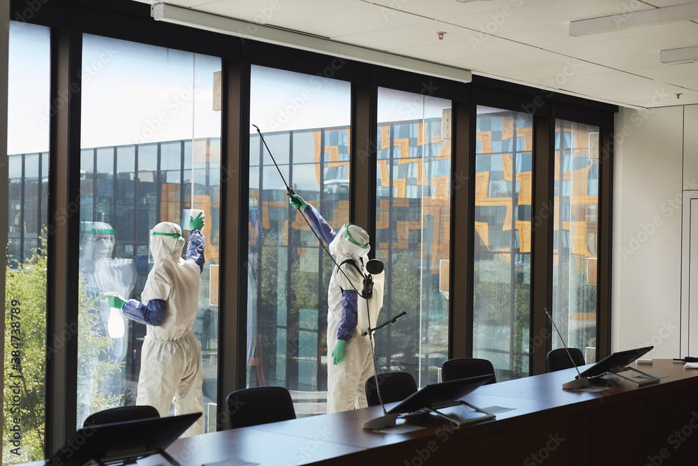 Fototapeta Wide angle portrait of two workers wearing hazmat suits disinfecting office windows in conference room, copy space