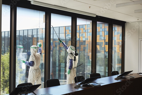 Obraz Wide angle portrait of two workers wearing hazmat suits disinfecting office windows in conference room, copy space - fototapety do salonu