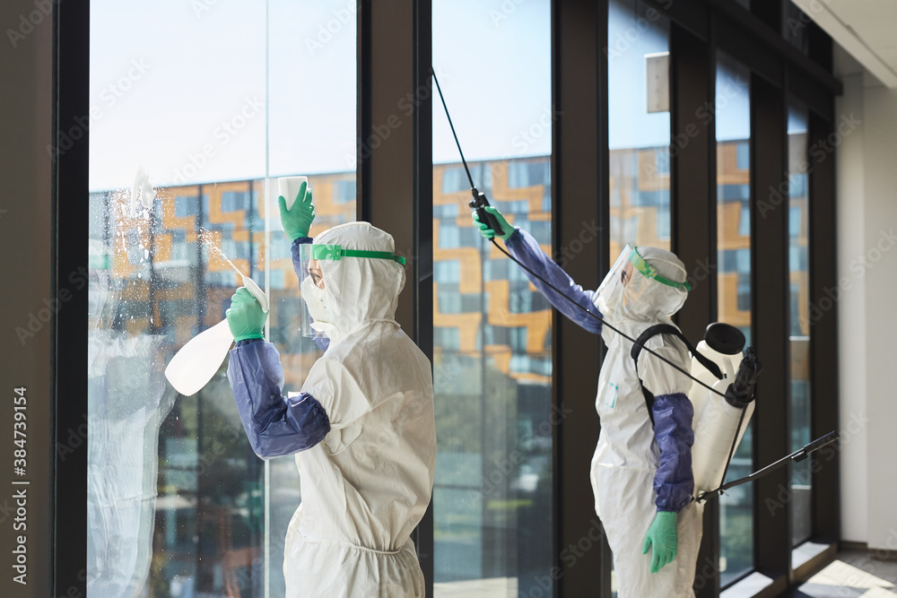 Fototapeta Portrait of two workers wearing hazmat suits disinfecting office windows in sunlight, copy space