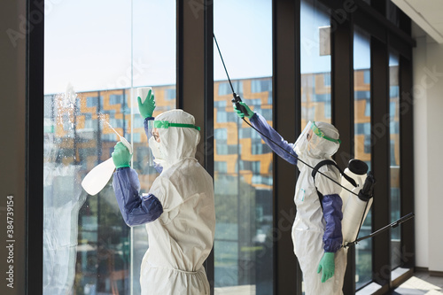 Obraz Portrait of two workers wearing hazmat suits disinfecting office windows in sunlight, copy space - fototapety do salonu