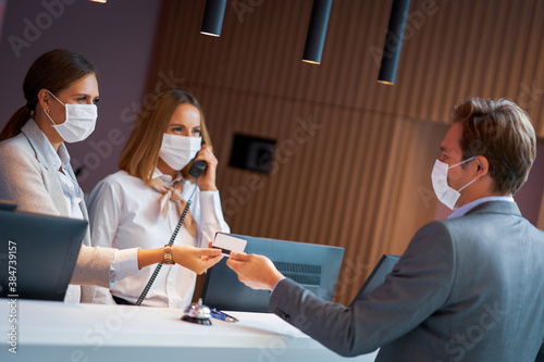 Businessman in mask at the reception of a hotel checking in Fototapet