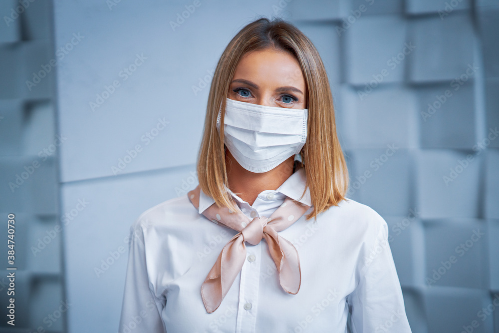 Fototapeta Female receptionist wearing face mask
