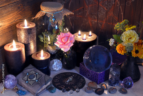 Mysterious still life with decorated diary book, black candles and zodiac chart on witch table.