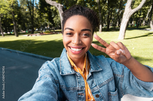 Valokuva Positive African Female Student Making Selfie Gesturing Victory-Sign In Park
