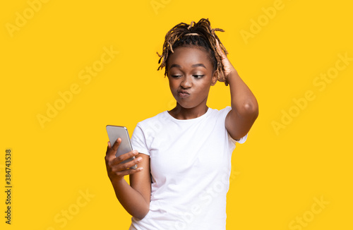 Confused african american woman looking at mobile phone screen