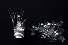Broken Incandescent Lamp On A Black Background. Shards Of Glass, Close-up Photo.