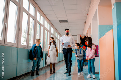 Obraz na płótnie Elementary school students and male teacher wearing protective face masks at sch