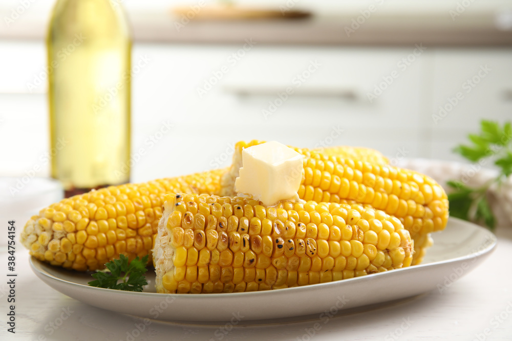 Fototapeta Fresh grilled corn cobs with butter on white wooden table, closeup
