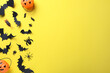 Halloween decor elements on yellow background, flat lay. Space for text