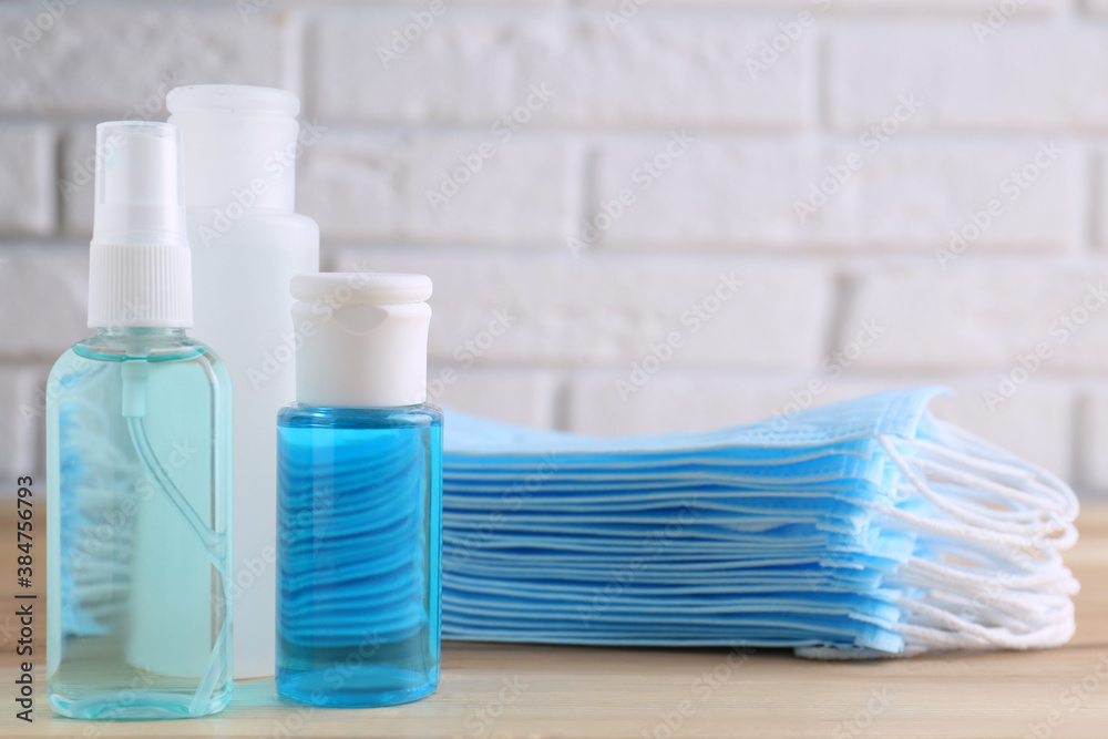 Fototapeta Hand sanitizers and respiratory masks on wooden table. Protective essentials during COVID-19 pandemic