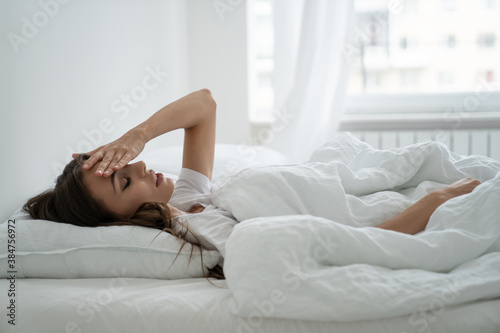 Unhappy exhausted young woman lying in bed touching forehead, suffering from insomnia, headache or migraine, feels tired not enough of rest, lack of sleep Wallpaper Mural