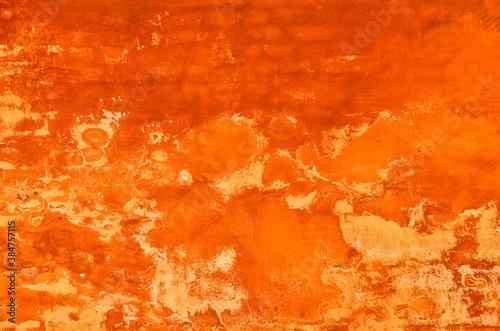 bright and vibrant orange coloured finery, plastering part of a wall, old and vi Fototapeta