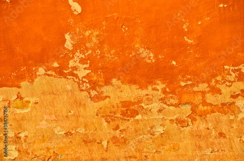Fotografija bright and vibrant orange coloured finery, plastering part of a wall, old and vi