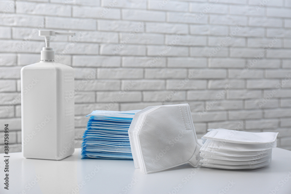 Fototapeta Hand sanitizer and respiratory masks on table near white brick wall. Protective essentials during COVID-19 pandemic