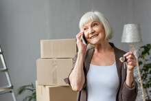 Happy Senior Woman Talking On Phone And Holding Keys In New House, Moving Concept