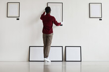 Full Length Back View At African-American Man Hanging Blank Frames On Wall While Planning Art Gallery Or Exhibition, Copy Space