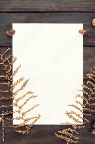 Fotografija Blank paper on wooden table and autumn decoration