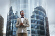Attractive black male businessman in a business suit against the backdrop of an office building.