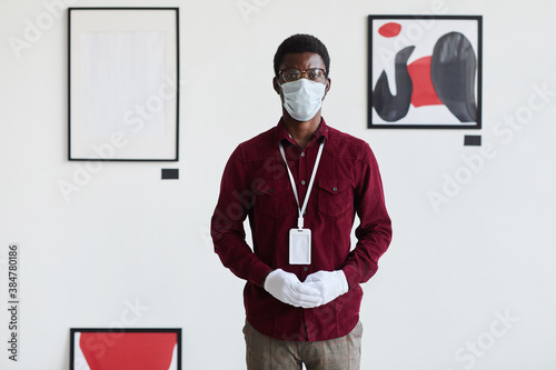 Front view portrait of African-American man wearing mask looking at camera while standing against modern graphic paintings in art gallery, copy space