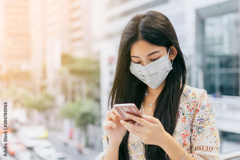 Fototapeta Beautiful Asian Business woman wearing surgical protective face mask using smart phone mobile Technology contact communication commuter transport urban building city life traveling to work copy space
