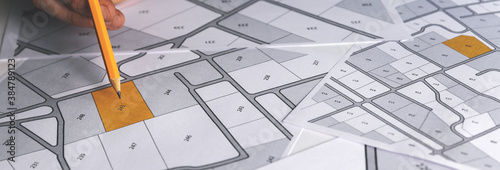 Obraz hand with pencil on cadastral map - choose and buy a building plot for house construction. banner copy space - fototapety do salonu