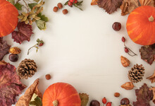 Frame Made Of Dried Leaves, Pumpkins, Pine Cones And Flowers On White Wooden Background. Autumn And Halloween Concept.