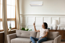 Smiling Asian Young Woman Using Air Conditioner Cooler System Remote Controller, Sitting On Cozy Sofa At Home, Relaxed Girl Switching, Setting Comfort Temperature In Living Room, Enjoy Fresh Air
