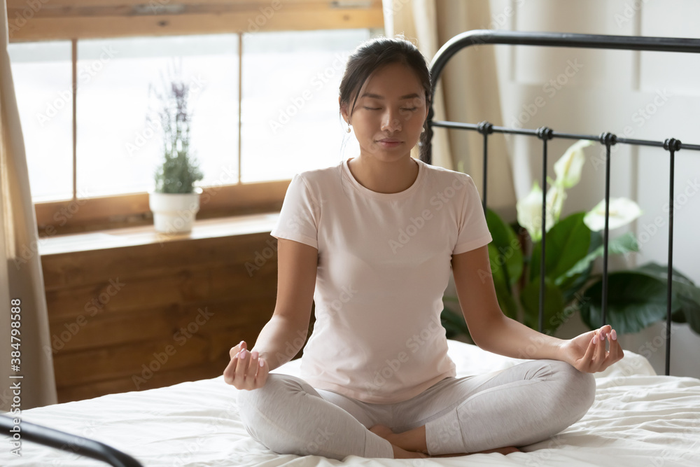 Fototapeta Calm peaceful Asian young woman meditating in bedroom alone, tranquil beautiful girl with closed eyes sitting in lotus pose on cozy bed, dreaming, doing yoga exercise, stress relief concept