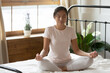 Leinwandbild Motiv Calm peaceful Asian young woman meditating in bedroom alone, tranquil beautiful girl with closed eyes sitting in lotus pose on cozy bed, dreaming, doing yoga exercise, stress relief concept