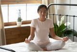 Calm peaceful Asian young woman meditating in bedroom alone, tranquil beautiful girl with closed eyes sitting in lotus pose on cozy bed, dreaming, doing yoga exercise, stress relief concept