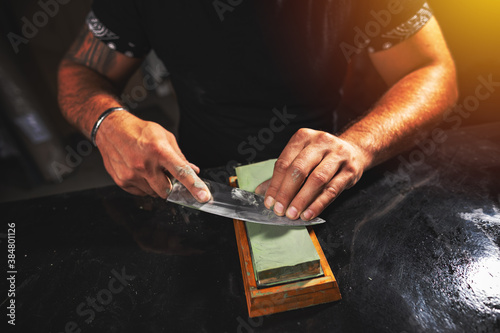 Man's hands sharpening knife #384801126