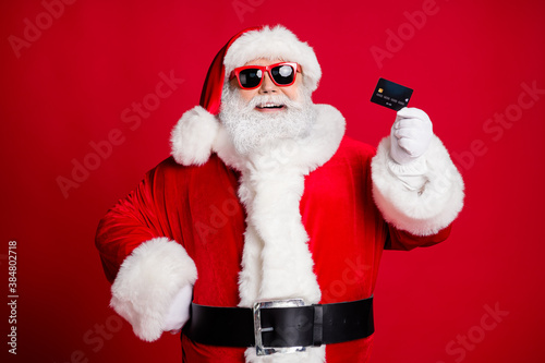 Close-up portrait of his he nice handsome cheerful cheery bearded Santa holding in hand using plastic card store shop cash back cashback isolated bright vivid shine vibrant red color background
