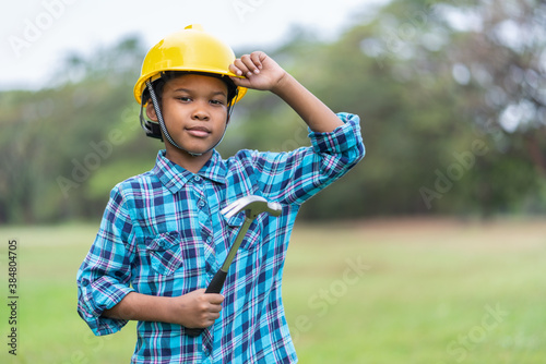Photo African American young boy in engineer holding hammer wearing a yellow safety helmet in the park