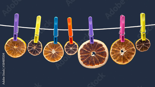 Fototapeta dried pieces of different citrus fruits hang on colored clothespins on a blue ba