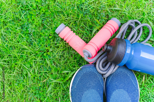 Obraz Jump rope, Running shoes, and drink bottle on grass background - fototapety do salonu