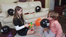 Girl Putting On A Clown Hat, Having Fun And Playingt,a Boy Is Inflating A Halloween Baloons. Children Get Ready For Celebrate Halloween At Home, Decorate Home