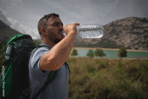 Fotomural Hiker drinking water from a bottle during a trail