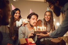 Young Man Blowing Candles On His Birthday Cake Surrounded By Happy Smiling Friends