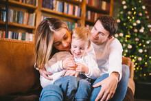 Happy Family On Sofa Near Book...
